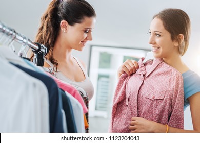 Cute young teen girlfriends shopping at the store and enjoying, one is holding a shirt