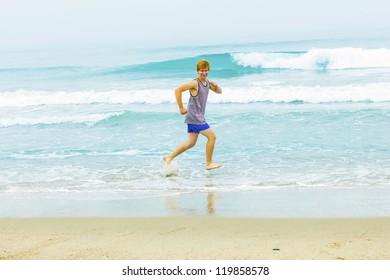 cute young teenage boy has fun at the beach