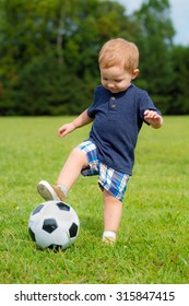 Cute young toddler playing soccer or football