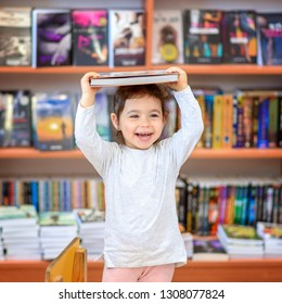 Cute Young Toddler Standing and Holding Book in Head. Little Happy Laughing Girl Indoors In Front Of Colorful Books. Child in a Library, Shop,Bookstore.