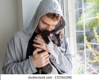 A cute young unshaven guy in a hoodie is holding a Cornish Rex cat in his arms. Love for pets, concept