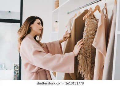 Cute young woman in bathrobe standing in front of hanger rack and trying to choose outfit dressing for work or walk. Selection of a wardrobe, stylist, shopping.