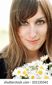 Cute young woman with bunch of daisies