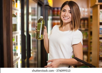 Cute young woman buying some water with chlorophyll at a grocery store