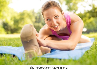 Cute young woman doing stretching exercises in the park. Selective Focus.