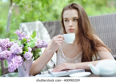 Cute young woman drinking coffee and resting in the garden