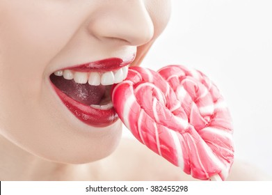 Cute young woman is eating sweet candy
