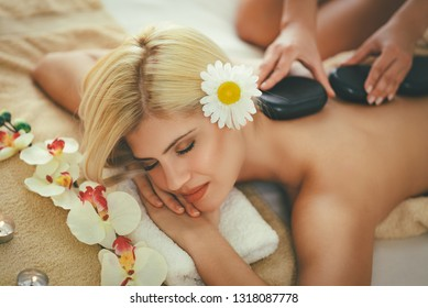 Cute young woman is enjoying during a back massage with warm stones at a spa.