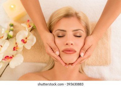Cute young woman enjoying during a facial care treatment at a spa.