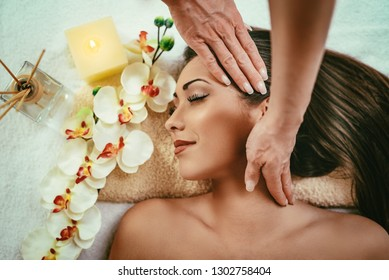 Cute young woman enjoying in head massage with her eyes closed.