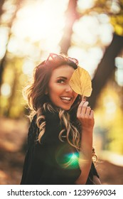 Cute young woman enjoying in sunny forest in autumn colors. She is holding golden leaf and looking at camer.