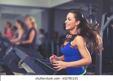 Cute young Young woman exercising on a treadmill at a gym
