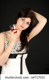 Cute young woman with glass of red wine over black background