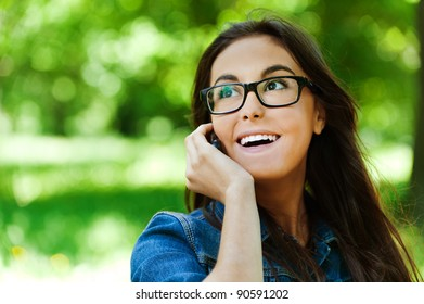cute young woman glasses park talking phone smiling
