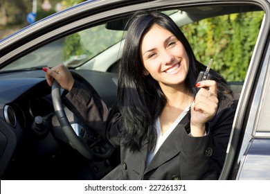 Cute young woman happy about new car