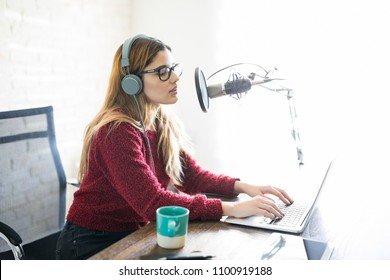 Cute young woman with headphone and laptop talking into a microphone