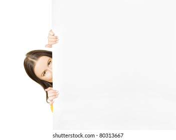 Cute Young Woman Hiding Behind A Blank Advertising Board Spying A Cheap Retail Bargain And Sales Discount, Isolated On White Background With Text Copyspace