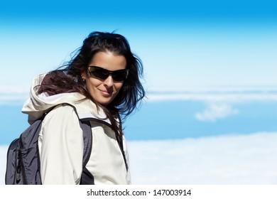 Cute Young Woman in High Mountain Range wit a Sea of Clouds