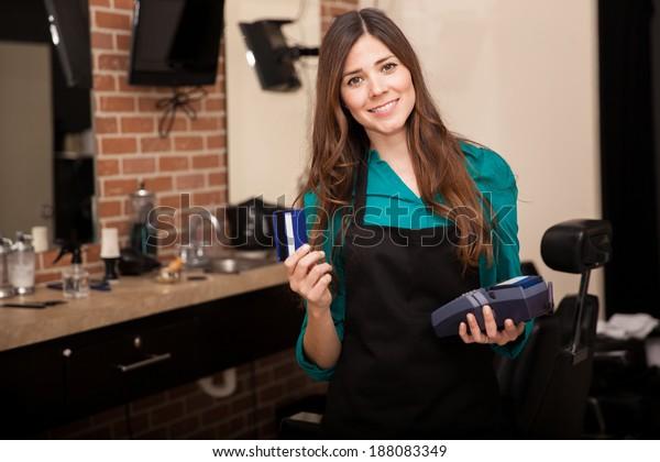 Kleine junge Frau mit Kreditkarte und Lächeln in einem Frisberladen