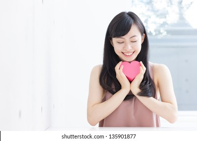 Cute young woman holding pink heart symbol