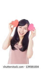 Cute young woman holding pink heart symbols against pale pink background