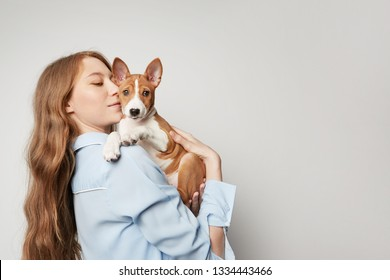 Cute young woman hugging and kissing her puppy basenji dog. Love between dog and owner. Isolated on white background.