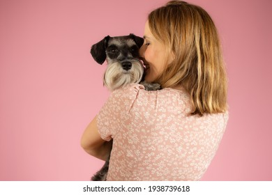 Cute young woman hugs her puppy schnauzer dog. Love between owner and dog isolated over pink background. Studio portrait.