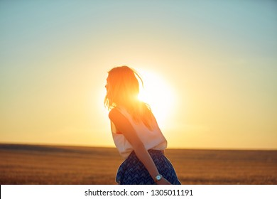 Cute young woman jumping in a wheat field.
