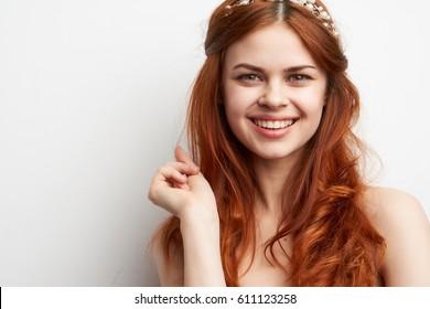 A cute young woman laughs beautifully at the camera