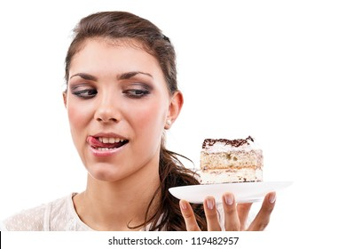 Cute young woman licking her lips with a delicious piece of cake