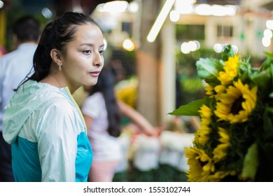 Cute young woman looking some sunflowers at flower market