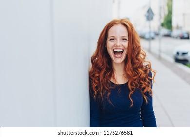 Schattige jonge vrouw met een heerlijk gevoel voor humor staande leunend tegen een witte buitenmuur met kopieerruimte in een stedelijke straat lachend om de camera