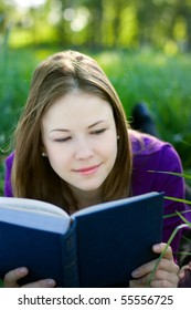 Cute young woman lying on the grass and reading a book