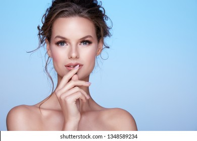 Cute young woman with naked shoulders and nude make up and curly hair posing at sky blue background, close up portrait, looking at camera.