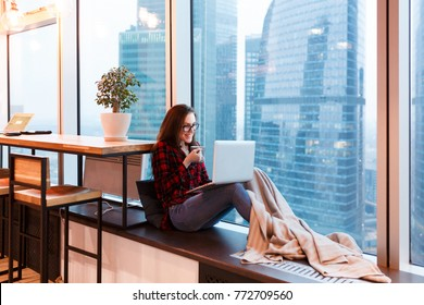 Cute young woman outsourcing designer working in creative studio sitting under blanket with mug of coffee and working at the computer on background of large window overlooking the skyscrapers