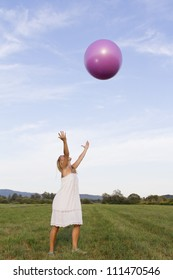 Cute young woman playing outdoors with pink fit-medicine ball