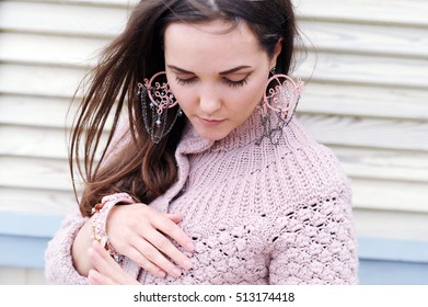 Cute young woman portrait dressed in gentle sweater and handmade pink boho style earrings, autumn outdoor fashion