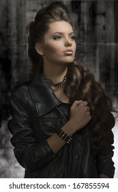 cute young woman posing in fashion portrait with modern leather jacket, rock accessories, long wavy hair-style. Dark look