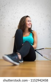 Cute young woman with a racket leaning against a wall in a squash court, ready for the game