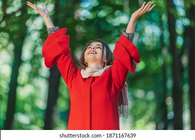 A cute young woman raising hands to the sky, rejoicing spring come and sunny weather over green blurred trees background.