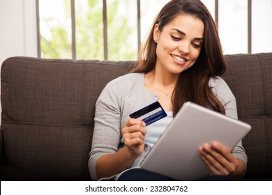 Cute young woman shopping online with her credit card and a tablet computer at home