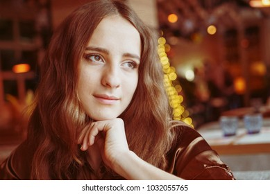 Cute young woman is sitting in a cafe and lookign through the window on a street. She has big brown eyes and nice brown long hair. Wearing a brown silk blouse. With light flares on the background.