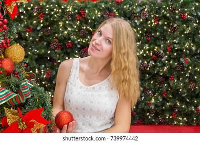 cute young woman sitting near christmas tree.