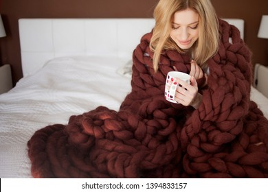 cute young woman is sitting on the bed wrapped in a big and fluffy brown plaid. Beautiful girl in a cozy blanket with a Cup of tea. Warmth and comfort of home, concept