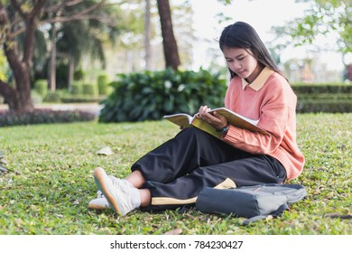 Cute young woman sitting on the grass and reading the book.