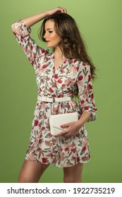 cute young woman in spring floreal dress, she is posing on green background keeping a white small bag