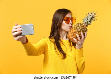 Cute young woman in sunglasses hold, kissing pineapple fruit doing selfie shot on mobile phone isolated on yellow orange background. People vivid lifestyle relax vacation concept. Mock up copy space
