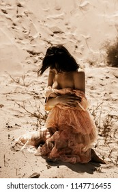 Cute young woman take off a dress and sits on a sand in desert
