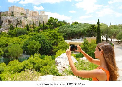 Cute young woman takes a picture of the Acropolis, Athens, Greece. Famous ancient Greek Acropolis is the main landmarks of Athens. Female tourist visits the Athens and takes a photo.