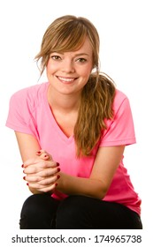 Cute Young Woman - This is a portrait of a beautiful young woman with her hair pulled back wearing a pink V-neck t-shirt. Shot on an isolate white background.